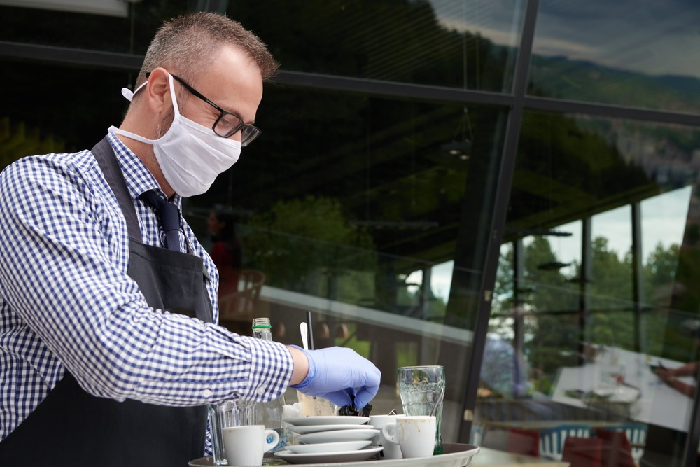 waiter in a medical protective mask serves the coffee in restau
