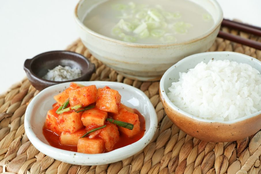 Korean meal consisting a bowl of kimchi, a bowl of rice, a bowl of soup, and a tiny bowl of condiment